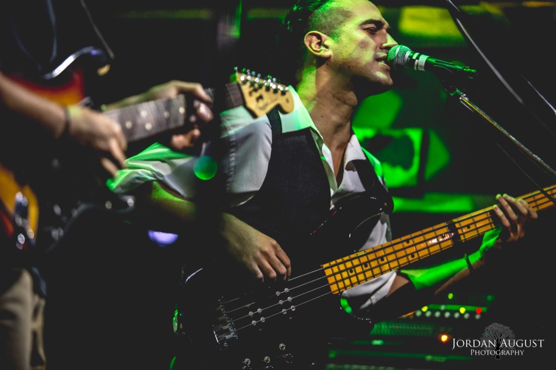Photo of Bassist Nik Playing Bass and Singing